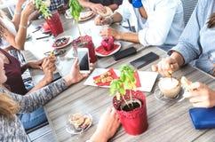 Верхний взгляд со стороны друзей выпивая капучино на ресторане кофейни - людях имея потеху совместно есть и используя мобильный т стоковое изображение