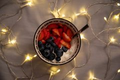 Верхний взгляд со стороны шара с йогуртом, клубниками и голубиками над серыми листами со светами стоковые изображения