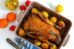 Верхний плоский взгляд зажаренного в духовке мяса утки с овощами в круглом керамическом баке на белой поверхности деревянного сто Стоковая Фотография RF