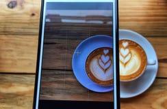 Верхний слой стрельбы изображения в телефоне и капучино реальной нерезкости горячем в белых чашке и поддоннике на предпосылке дер стоковые фото