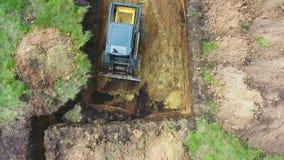 Верхний спуск мини затяжелителя выкапывает почву на травянистом поле для ямы учреждения нового дома сток-видео