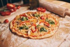 Верхняя пицца wiev лежит на текстурных woden таблица около разделочной доски a деревянной которые там все прерванные ингридиенты Стоковая Фотография
