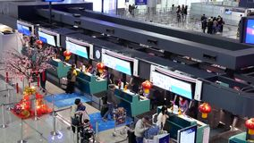 Верхняя съемка пассажиров идя к авиакомпании Китая проверяет внутри столы