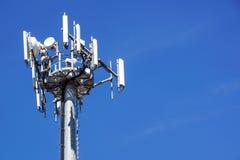 Верхняя часть башни связи сотового телефона с множественными антеннами против голубого неба Стоковая Фотография RF