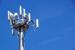 Верхняя часть башни связи сотового телефона с множественными антеннами против голубого неба Стоковая Фотография