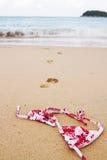 Верхняя часть бикини лежа на пляже с следами ноги в прибой Стоковая Фотография RF