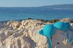Верхняя часть бикини лежа на утесе морем и голубым небом Стоковые Изображения