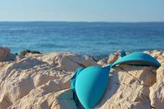 Верхняя часть бикини лежа на утесе морем и голубым небом Стоковая Фотография