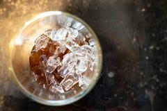 Верхняя часть вверх по взгляду куба льда в питье колы стеклянном стоковые изображения rf