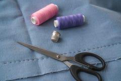 Верхняя часть взгляда отрезанной части юбки с зашитой вытачкой, ножницами, кольцом и 2 катышками потока 2 катышкы пинка и пурпурн стоковая фотография