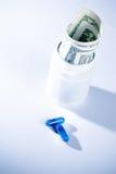Верхняя часть взгляда голубых пилюлек перед контейнером с внутренностью свернула вверх по долларам на белой предпосылке Стоковое Изображение RF