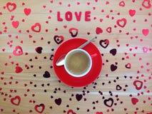 Верхняя часть взгляда декоративных красных сердец приближает к чашке кофе на деревянном столе Стоковая Фотография