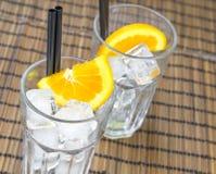 Верхняя часть взгляда пустых стекел коктеиля с 2 оранжевыми кусками и кубами льда Стоковое Фото