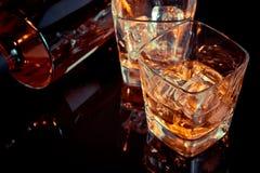 Верхняя часть взгляда стекла вискиа около бутылки на черной таблице с отражением, старым стилем Стоковые Фото