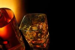 Верхняя часть взгляда стекла вискиа около бутылки на черной таблице с отражением Стоковые Фотографии RF