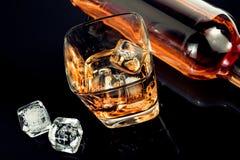 Верхняя часть взгляда стекла вискиа около кубов бутылки и льда на черной таблице с отражением Стоковое фото RF