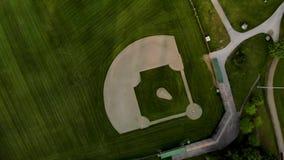 Верхняя часть вниз с взгляда зеленого поля бейсбола между деревьями которое в настоящее время незанятый - 4K видеоматериал