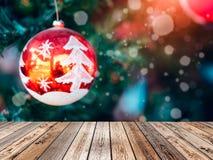 Верхняя часть деревянного стола на запачканном шарике рождества на дереве с shi снега Стоковые Фотографии RF