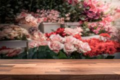 Верхняя часть деревянного стола/счетчик магазина перед запачканным магазином цветка стоковые изображения rf