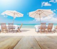 Верхняя часть деревянного стола с нерезкостью комплекта и зонтика таблицы на пляже Стоковые Изображения