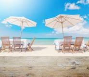 Верхняя часть деревянного стола с нерезкостью комплекта и зонтика таблицы на пляже Стоковая Фотография RF