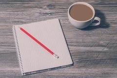 Верхняя часть над концом накладных расходов вверх по предпосылке фото взгляда открытых тетради, карандаша и чашки горячего кофе н стоковое изображение