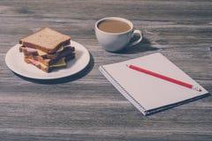 Верхняя часть над phot взгляда накладных расходов остатков пролома ослабляет закуску на работе Сандвич сыра с чашкой белого кофе, Стоковое Фото