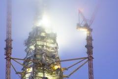 Верхняя часть небоскреба во время конструкции с кранами здания положена в кожух в облака и туман на ноче Стоковые Изображения