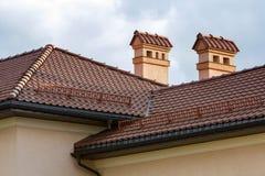 Верхняя часть нового большого просторного современного дома с постриженной красной крышей, 2 высокими печными трубами, заштукатур стоковое фото rf