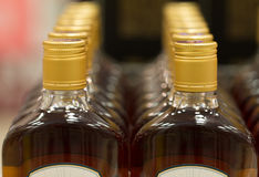 Верхняя часть пластичных бутылок при коньяк или рябиновка стоя в винном магазине От фронта Стоковые Фото