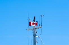 Верхняя часть рангоута корабля металла с канадским флагом на голубом небе Стоковое фото RF