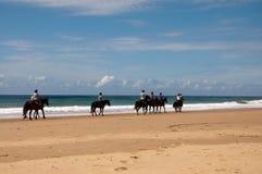 Верховые лошади людей вдоль берега океана Стоковая Фотография