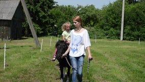 Верхом езда пони девушки