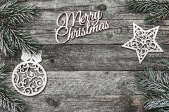 Верхушка, верхняя часть, осматривает сверху белых figurines зимы, вечнозеленой ветви и с Рождеством Христовым надписи на серой пр Стоковое фото RF
