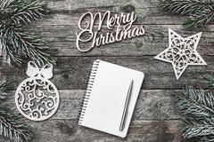Верхушка, верхняя часть, осматривает сверху белых figurines зимы, вечнозеленой ветви, блокнота, ручки и с Рождеством Христовым на Стоковое Изображение