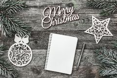 Верхушка, верхняя часть, осматривает сверху белых figurines зимы, вечнозеленой ветви, блокнота, ручки и с Рождеством Христовым Стоковое Фото