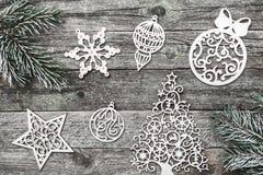 Верхушка, верхняя часть, осматривает сверху белых figurines зимы, вечнозеленой ветви на серой предпосылке Стоковое Фото