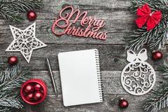 Верхушка, верхняя часть, осматривает сверху белых figurines зимы, вечнозеленой ветви, блокнота, ручки, красного смычка, игрушек и Стоковые Изображения