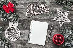 Верхушка, верхняя часть, осматривает сверху белых figurines зимы, вечнозеленой ветви, блокнота, ручки, красного смычка, игрушек и Стоковая Фотография RF