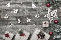 Верхушка, верхняя часть, осматривает сверху белых figurines зимы, вечнозеленой ветви, игрушек красного цвета, настоящих моментов  Стоковые Фото