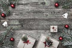 Верхушка, верхняя часть, осматривает сверху белых figurines зимы, вечнозеленой ветви, игрушек красного цвета, настоящих моментов  Стоковые Изображения