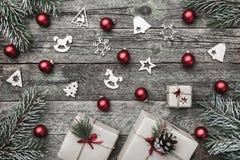 Верхушка, верхняя часть, осматривает сверху белых figurines зимы, вечнозеленой ветви, игрушек красного цвета, настоящих моментов  Стоковое фото RF