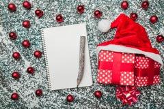 Верхушка, верхняя часть, осматривает сверху блокнота, деревянной винтажной ручки, вечнозеленых красных игрушек, шляпы подарков на Стоковые Фото