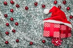 Верхушка, верхняя часть, осматривает сверху, вечнозеленые красные игрушки, шляпа подарков на рождество и Санты на серой мраморной Стоковые Изображения