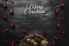 Верхушка, верхняя часть, осматривает сверху, вечнозеленых сосен, игрушек красного цвета и белой с Рождеством Христовым надписи Стоковые Изображения RF