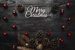 Верхушка, верхняя часть, осматривает сверху, вечнозеленых сосен, игрушек красного цвета и белой с Рождеством Христовым надписи Стоковые Изображения