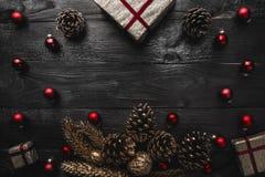 Верхушка, верхняя часть, осматривает сверху, вечнозеленых сосен, игрушек красного цвета и подарка на рождество на черной деревянн Стоковая Фотография RF