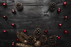 Верхушка, верхняя часть, осматривает сверху, вечнозеленых сосен, игрушки красного цвета на черной деревянной предпосылке Стоковые Фотографии RF