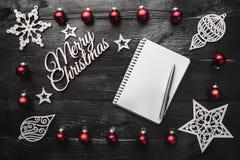 Верхушка, верхняя часть, осматривает сверху, деревянных figurines зимы, игрушек красного цвета, блокнота, ручки и белой с Рождест Стоковое Изображение RF