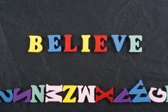 ВЕРЬТЕ слову на черной предпосылке доски составленной от писем красочного блока алфавита abc деревянных, копируйте космос для тек Стоковое фото RF